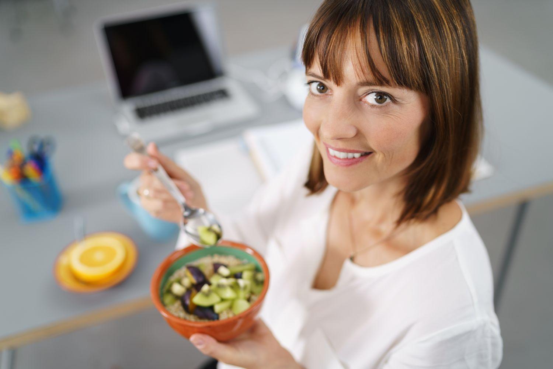 vrouw met bakje fruit op het werk